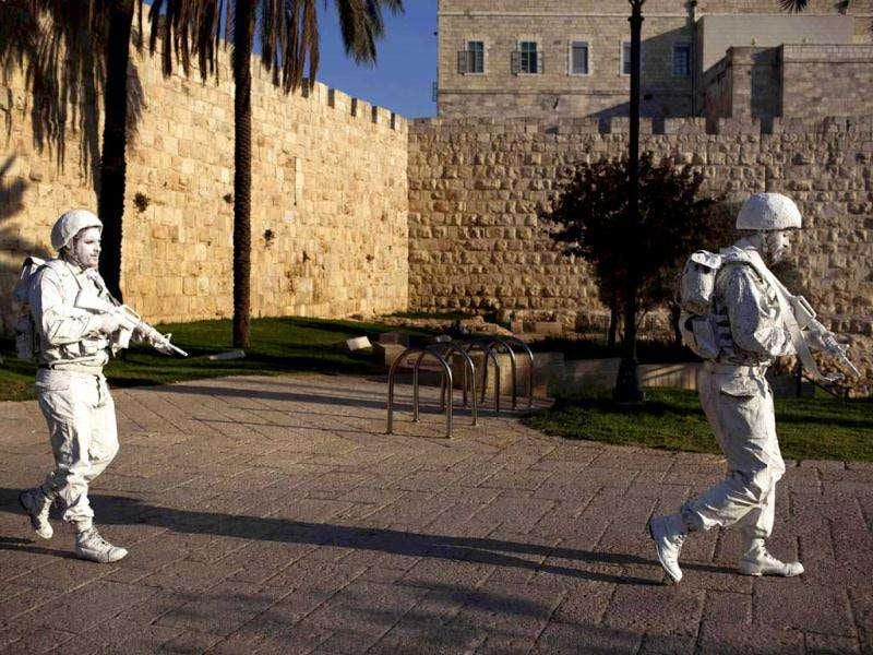 "Israeli artists Yuda Braun (R) and Jonathan Peleg patrol next to Jerusalem's Old City walls as part of their artistic performance ""The White Soldiers patrol Nomansland""."