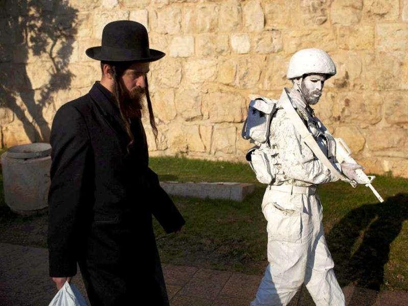 "Israeli artist Yuda Braun (R) walks past an Ultra Orhtodox Jewish man next to Jerusalem's Old City walls as part of his artistic performance ""The White Soldiers patrol Nomansland""."