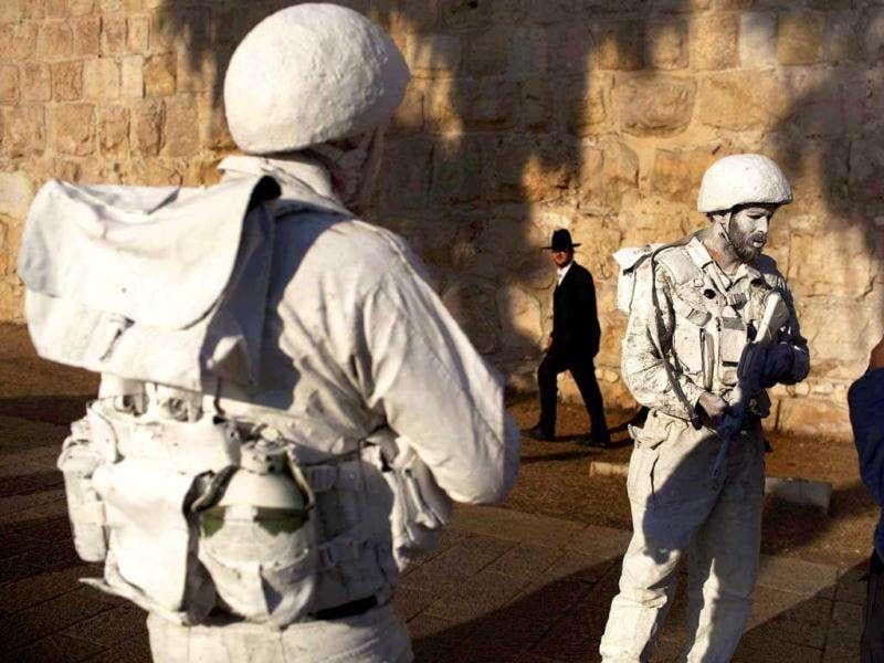 "An Israeli border guard (R) talks to Israeli artists Yuda Braun (C) and Jonathan Peleg as they patrol next to Jerusalem's Old City walls as part of their artistic performance ""The White Soldiers patrol Nomansland""."