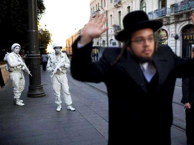 "An Ultra Orthodox Jewish man walks near Israeli artists Yuda Braun (R) and Jonathan Peleg as they perform ""The White Soldiers patrol Nomansland"" in mostly Jewish west Jerusalem."
