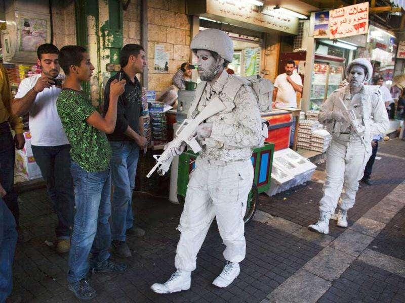 Artists Yuda Braun, front, and Jonathan Pelleg, walk in Jerusalm as a part of performance titled