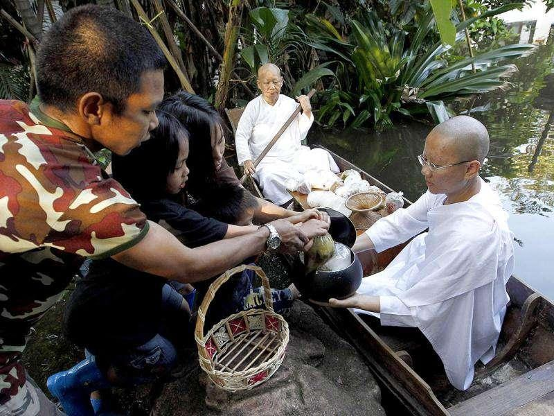 Buddhist nuns receive food from people as they sit in a boat on floodwaters at the Sathira-Dhammasathan Buddhist meditation centre in Bangkok1. As waterlogged Thailand struggles to contain the worst floods in decades, it faces a simple truth: not a whole lot can be done to avoid a repeat disaster in the short term even with a new multi-billion dollar water-management policy.