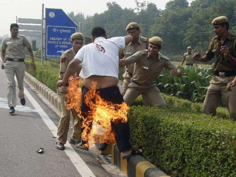 Police try to douse flames on a Tibetan demonstrator after he tried to self immolate himself during a protest in front of the Chinese embassy in New Delhi.
