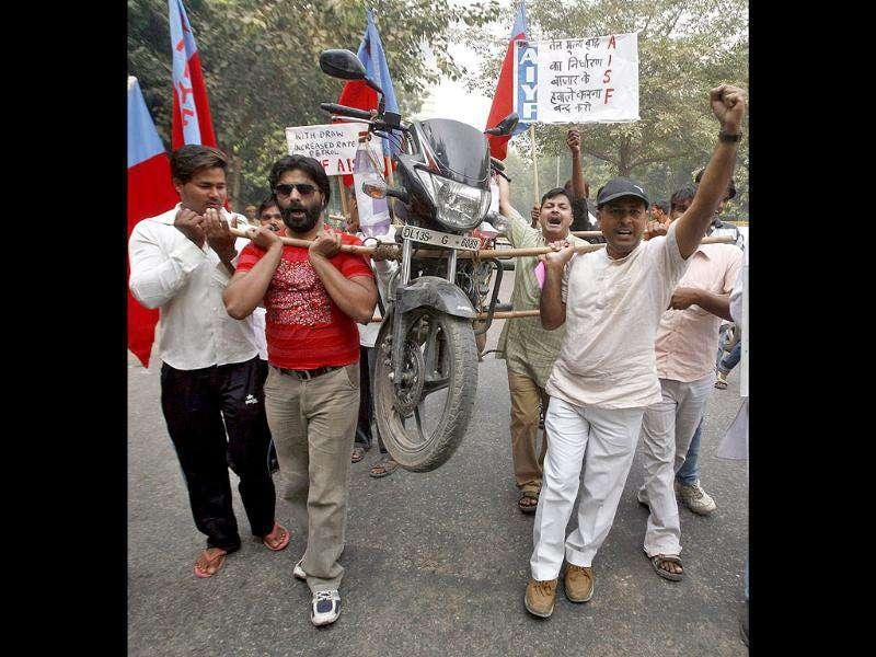 Demonstrators carry a motor bike with the help of bamboo sticks to protest a price hike in petrol in New Delhi. The placard on the right reads