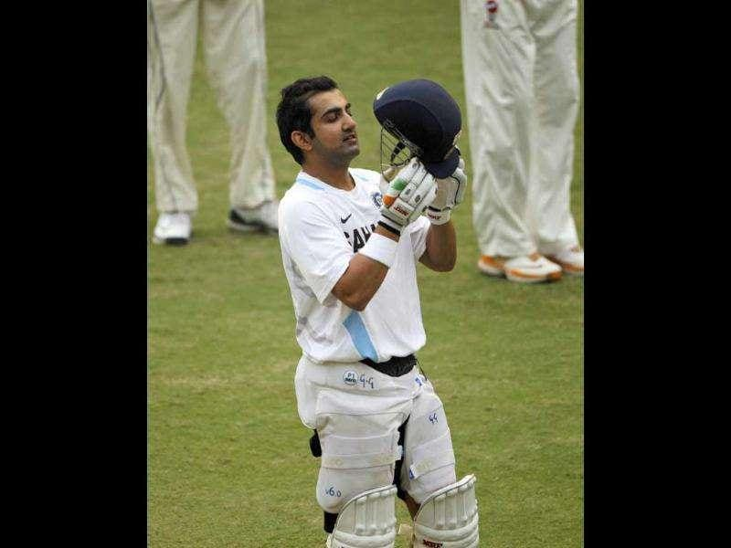 Cricketer Gautam Gambhir puts on a helmet during a practice session in New Delhi.