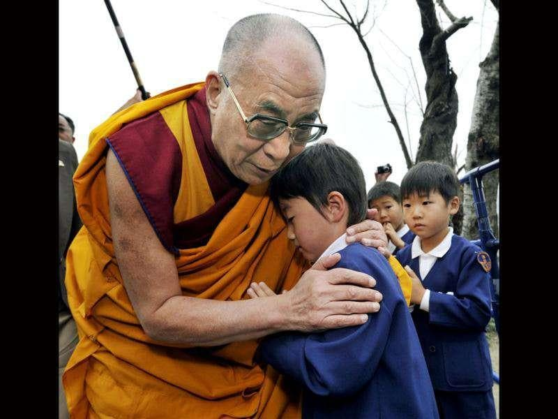 Tibetan spiritual leader the Dalai Lama, left, hugs a child at a temple at Ishinomaki, Northeastern Japan, where the Buddhist leader conducted a memorial service for the victims of the March 11 earthquake and tsunami disaster.