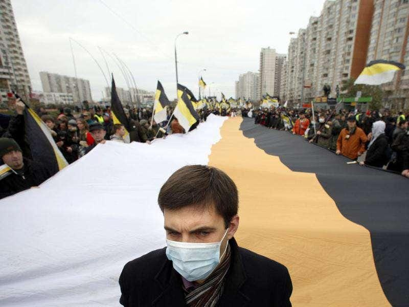 Ultra nationalist demonstrators and activists march carrying the Russian Empire's black-yellow-white flags to mark National Unity Day, on the outskirts of Moscow, Russia.