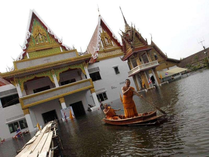 Buddhist monks travel on a boat at a flooded temple in Bangkok. The floods in Thailand began in July and have devastated large parts of the central Chao Phraya river basin, killed nearly 400 people and have disrupted the lives of more than two million.
