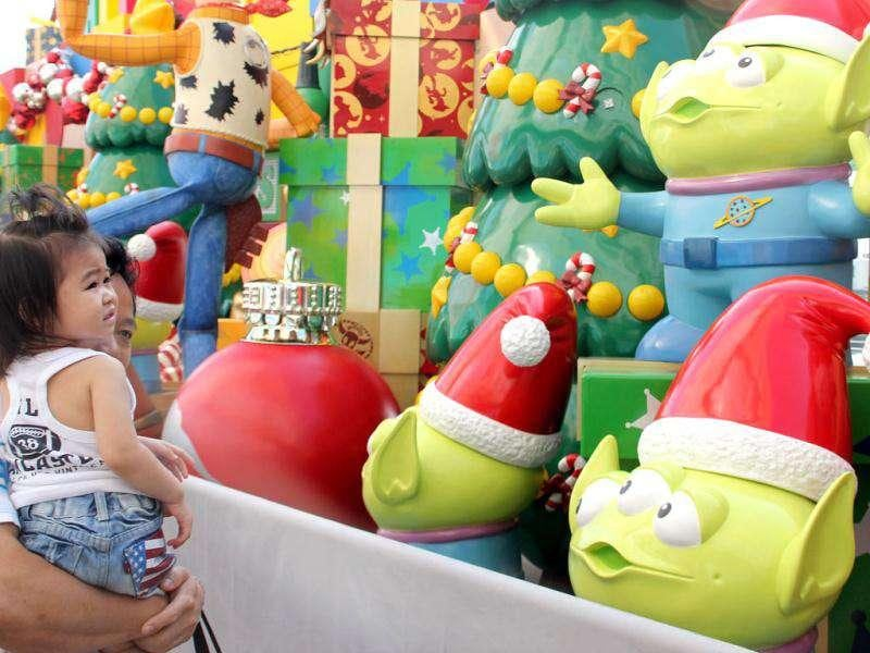 A man holds his daughter to view characters from Disneyland's Toy Story theme outside a shopping mall in Hong Kong. Disneyland's new attraction Toy Story Land, which is based on the popular animated film, is due to open in mid November.