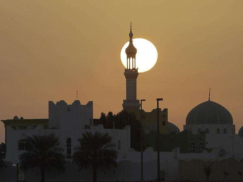 Sun rises behind a minaret on Abu Dhabi- Dubai highway, United Arab Emirates. Muslims celebrate Eid Al-Adha.