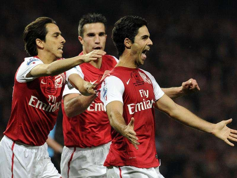 Arsenal's Mikel Arteta, right, celebrates scoring against West Bromwich Albion with Robin van Persie, center, and Yossi Benayoun during their English Premier League soccer match at the Emirates stadium, London.