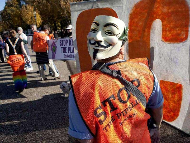 A demonstrator wearing a Guy Fawkes mask on the back of her head, calls for the cancellation of the Keystone XL pipeline during a rally in front of the White House in Washington. Protesters are unhappy about TransCanada Corp's plan to build the massive pipeline to transport crude from Alberta, Canada, to Texas.