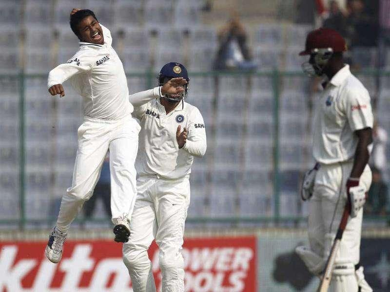India's Pragyan Ojha (L) celebrates with his teammate VVS Laxman after dismissing West Indies captain Darren Sammy (R) during the second day of their first test cricket match in New Delhi.