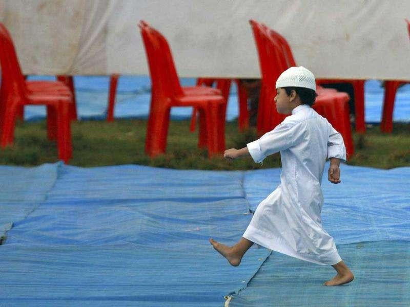 A boy walks on a plastic sheet as he arrives for Eid al-Adha prayers at a field in the southern Indian city of Kochi.