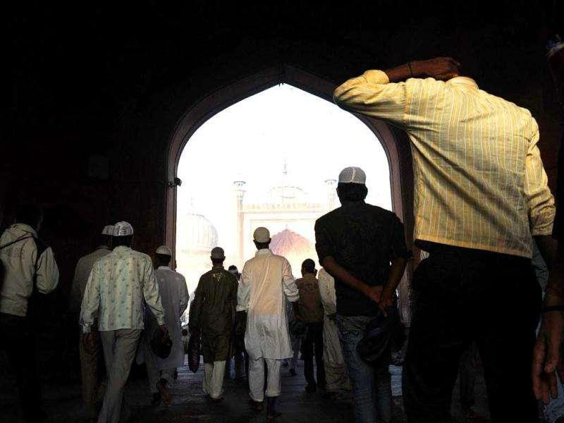 Faithful Muslim followers walk into the the inner courtyard of the 17th century Jama Masjid mosque in New Delhi.