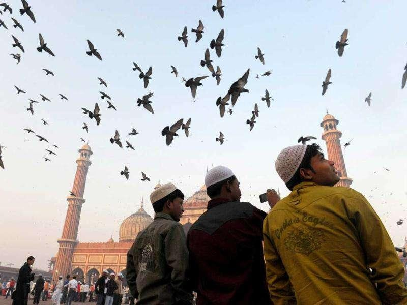 Three boys watch doves fly over the inner courtyard of the 17th century Jama Masjid mosque prior to early morning Eid al-Adha prayers in New Delhi.