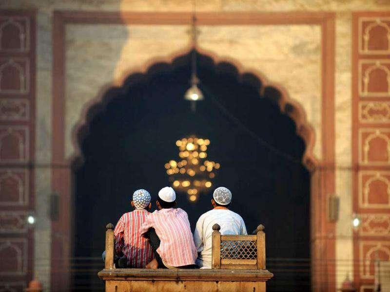 Three boys sit near an entrance to the inner courtyard of the 17th century Jama Masjid mosque in New Delhi as they wait for morning Eid al-Adha prayers.
