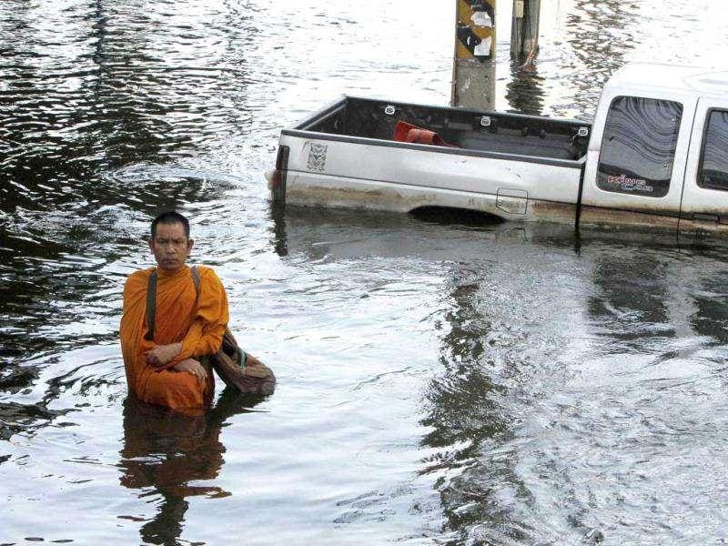 A Buddhist monk walks down a flooded street while collecting alms in Bangkok. Thailand's worst floods in half a century have killed nearly 400 people since mid-July.