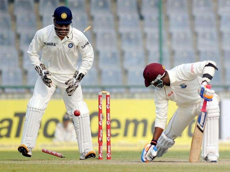 Indian cricket captain Mahendra Singh Dhoni (L) celebrates the dismissal of West Indies cricketer Marlon Samuels (R) during the third day of the First Test Match at the Feroz Shah Kotla stadium in New Delhi.