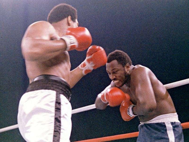 In this file photo, heavyweight boxer Joe Frazier grimaces after Muhammad Ali, left, landed a blow to Frazier's head during their boxing bout in Manila, the Philippines. Ali won the fight after Frazier's manager stopped the fight in the 14th round. (AP Photo/File)