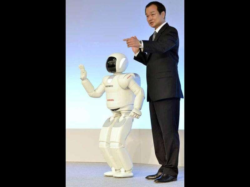 Honda president Takanobu Ito poses with the company's humanoid robot 'Asimo' after demonstration of the robot's new fuctions at the company's laboratory in Wako city , suburban Tokyo on November 8, 2011. The new Asimo can move without being conytolled by an operator.