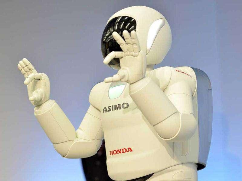 A Honda robot named 'Asimo' performs sign langage during a demonstration of its new fuctions, at the company's laboratory in Wako city, suburban Tokyo. The new Asimo can move without being controlled by an operator after its 'intelligence' and physical ability to adapt to situations was improved.