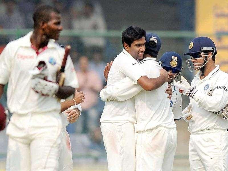 Indian cricketer Ravichandan Ashwin (2L) celebrates with teammates after taking the wicket of West Indies cricket captain Darren Sammy (L) during the third day of the First Test Match at the Feroz Shah Kotla stadium in New Delhi.