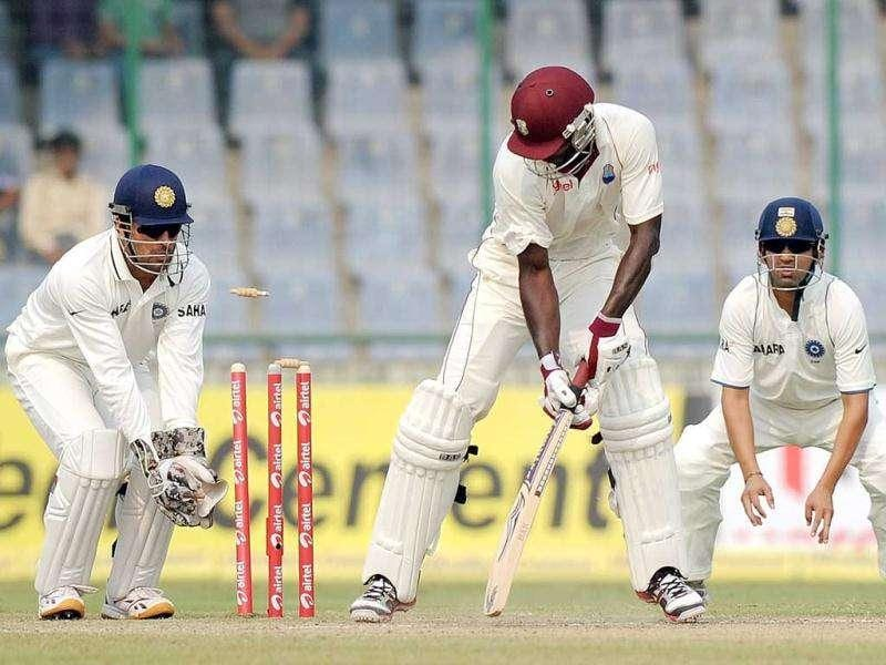 West Indies cricket captain Darren Sammy (C) is bowled out by unseen Indian cricketer Ravichandran Ashwin during the third day of the First Test Match at the Feroz Shah Kotla stadium in New Delhi.