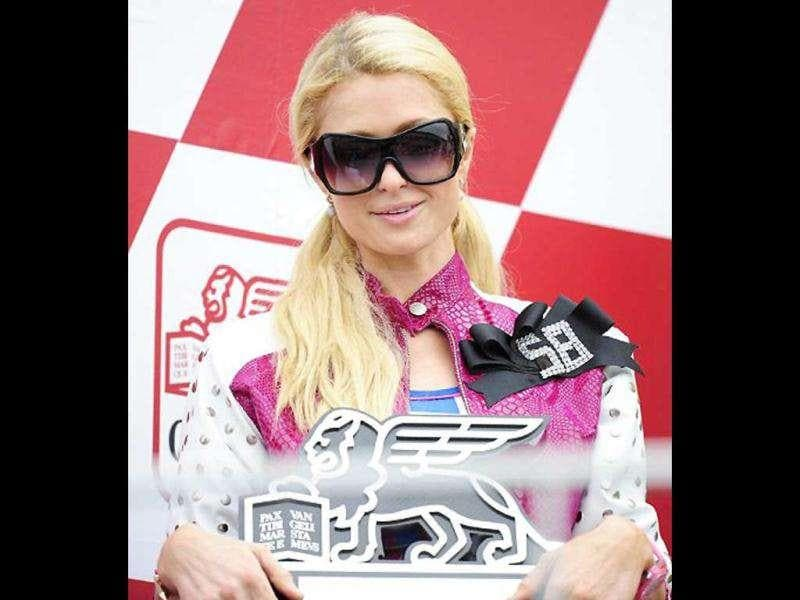 The socialite poses on the podium of the 125cc race.