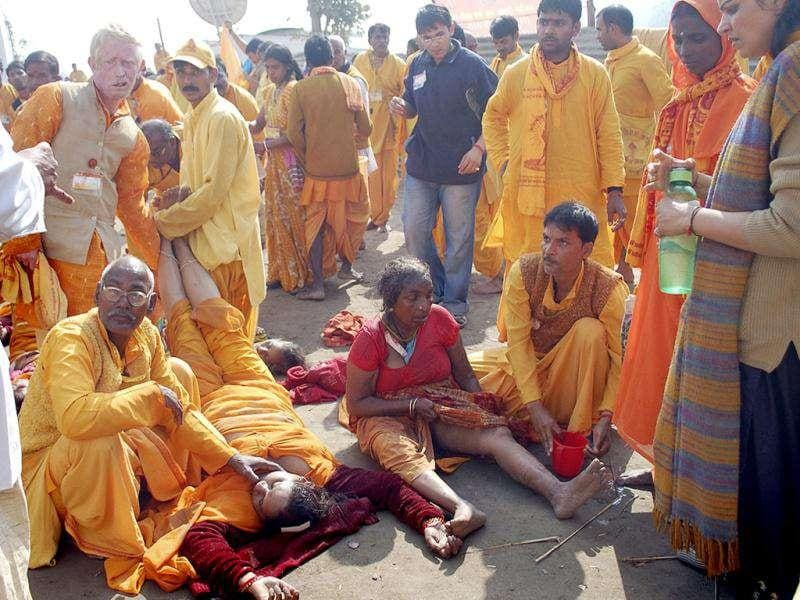 Devotees lift the feet of a devotee, second left front, who was killed in a stampede, as another tends to an injured on the banks of the River Ganges in Haridwar.