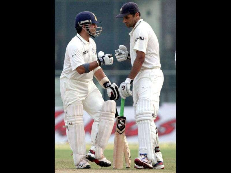 Sachin Tendulkar (L) celebrates a shot with teammate Rahul Dravid during the third day of the first cricket test match against West Indies in New Delhi.