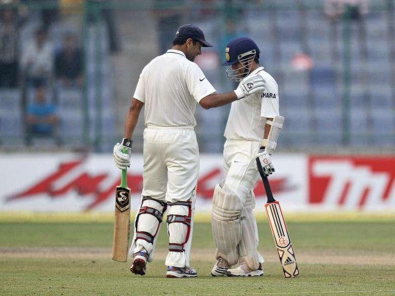 Batsman Rahul Dravid congratulates Sachin Tendulkar after he completed 15,000 runs in test cricket on the third day of the first of three test match series between India and West Indies in New Delhi.