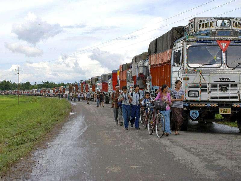 Schoolchildren and others walk past empty trucks parked in a row, waiting to be escorted by police to Assam to ferry supplies to Manipur, on the outskirts of Imphal. A three-month highway blockade by tribal agitators has created serious shortages of essential supplies.