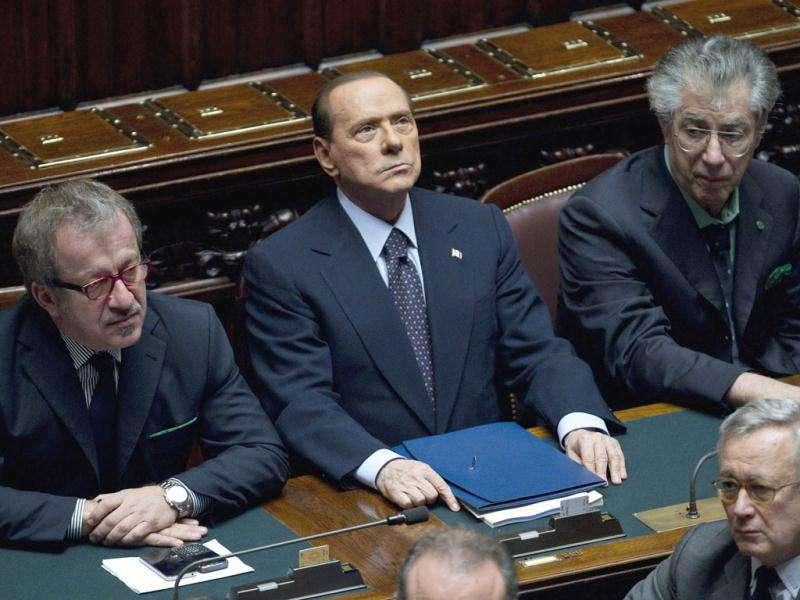 Italian Premier Silvio Berlusconi, center, flanked by interior minister Roberto Maroni, left, and reforms minister Umberto Bossi attends a voting session at the Lower Chamber, in Rome.
