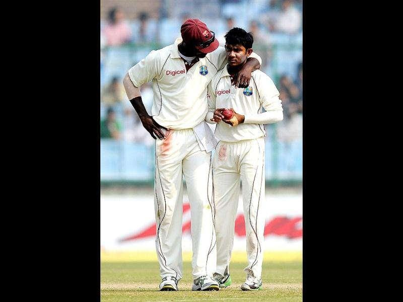 West Indies captain Darren Sammy (L) talks with teammate Devendra Bishoo (R) during the fourth day of the first cricket test match in New Delhi.