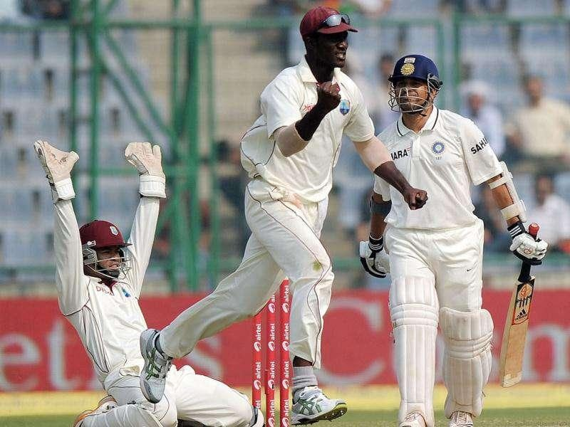West Indies captain Darren Sammy (C) and wicket keeper Carlton Baugh (L) celebrate the dismissal of Sachin Tendulkar (R) during the fourth day of the first cricket test match between India and the West Indies in New Delhi.