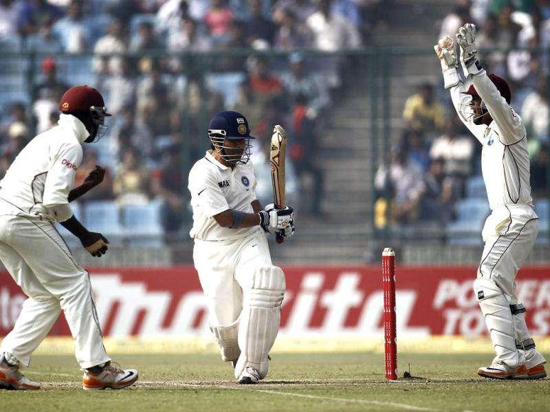 West Indies wicket keeper Carlton Baugh (R) and Darren Bravo successfully appeals for the dismissal of India's Sachin Tendulkar (C) during the fourth day of their first test cricket match in New Delhi.