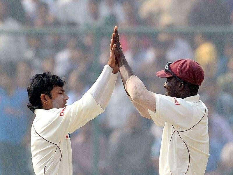 West Indies Devendra Bishoo celebrates the wicket of Sachin Tendulkar with captain Darren Sammy (L) during the fourth day of the first cricket Test match in New Delhi.