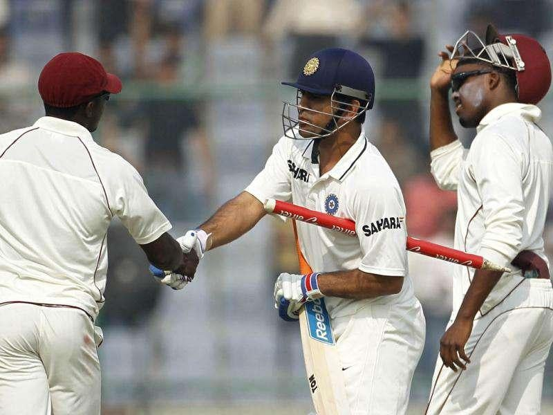 Mahendra Singh Dhoni shakes hands with West Indies' Fidel Edwards (L) as Darren Bravo watches after India won the first Test cricket match in New Delhi.
