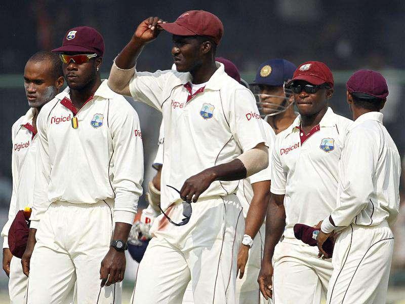 West Indies' captain Darren Sammy adjusts his cap as he leaves the field with his team mates after India won the first test cricket match in New Delhi.