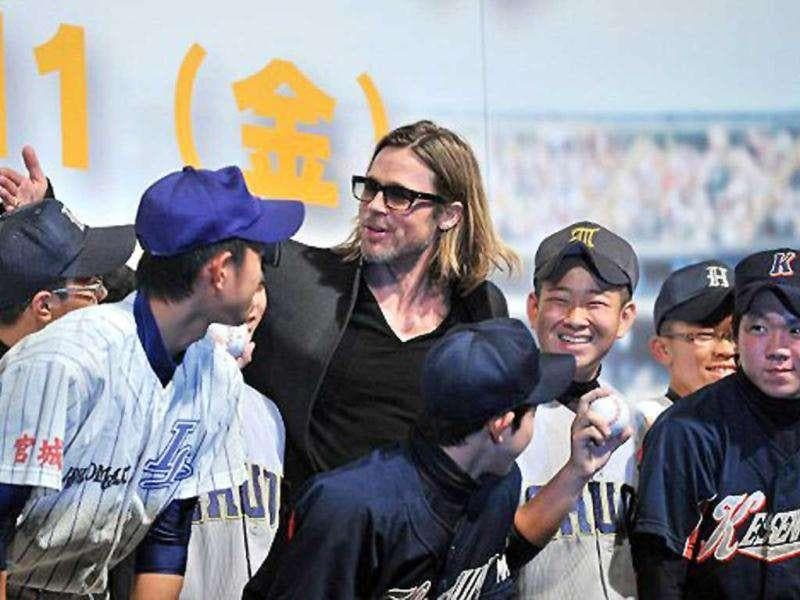 Brad Pitt poses with Japanese school baseball players.