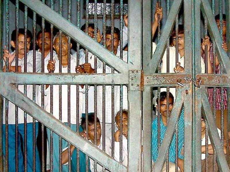 (File) A group of men convicted in connection with the murder of Muslims during riots on 04 March 2002 near Godasar in Gujarat, peers through the bars through the bars of their cell following sentencing at the district court in Nanidad, some 65 Kms south of Ahmedabad, 25 November 2003. AFP Photo