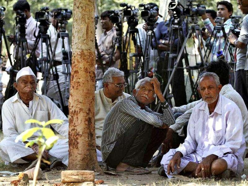 Unidentified relatives of accused and TV cameramen wait outside the district court in Mehsana, about 40 kilometers (25 miles) north of Ahmadabad. The court convicted 31 people for killing dozens of Muslims by setting a building on fire in Gujurat state nine years ago. AP Photo/Ajit Solanki