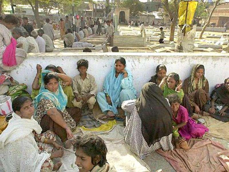 (File) Homeless people whose houses were burnt during recent riots sit at camp Bapu Nagar in Ahmedabad on 02 March 2002. The state-wide death toll in Hindu-Muslim clashes following a 27 February train attack in Gujarat which killed 58. AFP Photo/Indranil Mukherjee
