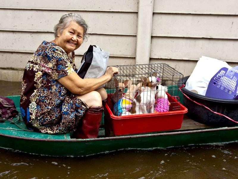 A woman carries her belongings on a boat in floodwater in Bangkok. The Thai capital, built on swampland, is slowly sinking and the floods currently besieging Bangkok could be merely a foretaste of a grim future as climate change makes its impact felt, experts say.