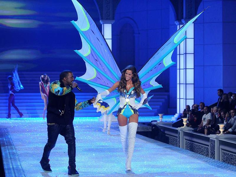 Kanye West holds a model's hand as he performs during the Victoria's Secret fashion show in New York.