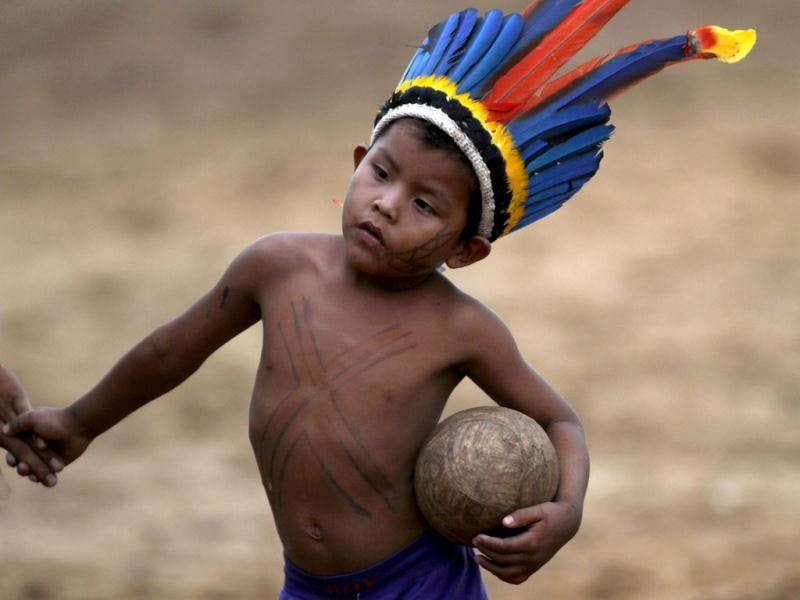 A Paresin Indian youth holds a soccer ball during the Indigenous Games on the island of Porto Real in the city of Porto Nacional, Brazil.