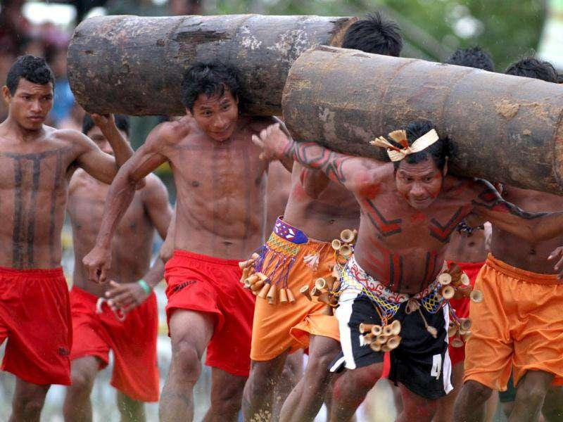 Xerente and Gaviao Indians race carrying tree trunks during the Indigenous Games on the island of Porto Real in the city of Porto Nacional, Brazil.