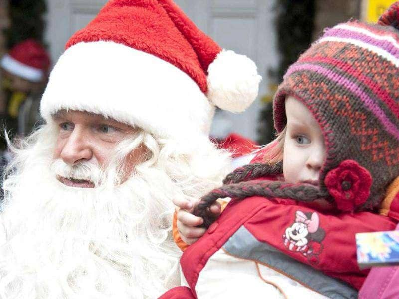 A man dressed up as Santa Claus holds a young child in front of the Santa Claus post office in the Eastern German town of Himmelpfort (Heaven's Gate). Children can send their Christmas wish lists to Himmelpfort from around the world and receive a reply from Santa. AFP Photo / John Macdougall
