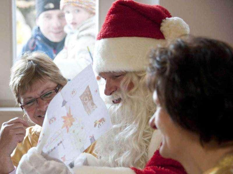 A man dressed as Santa Claus sits with his 'helpers' who are busy answering children's letters in the Santa Claus post office in the Eastern German town of Himmelpfort (Heaven's Gate). Children can send their Christmas wish lists to Himmelpfort from around the world and receive a reply from Santa. AFP Photo / John Macdougall